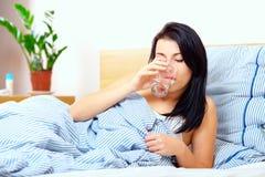 La jolie fille boit l'eau douce pendant le matin Photo stock