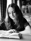 La jolie fille d'étudiant lit un livre dans un café photographie stock libre de droits