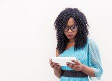 La jolie fille d'afro-américain regarde son ordinateur portable Photos stock