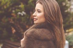 La jolie fille de l'adolescence utilise le manteau de fourrure image stock