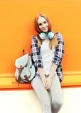 La jolie fille de sourire de mode avec des écouteurs écoute la musique Photo stock