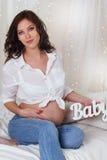 La jolie fille enceinte tient le bébé en bois de lettres Photo libre de droits