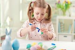 La jolie fille heureuse d'enfant ayant l'amusement pendant la peinture eggs pour Pâques au printemps Photo libre de droits