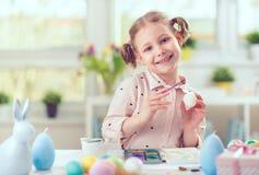 La jolie fille heureuse d'enfant ayant l'amusement pendant la peinture eggs pour l'est Photo stock