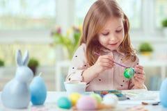 La jolie fille heureuse d'enfant ayant l'amusement pendant la peinture eggs pour l'est Photos libres de droits