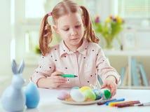 La jolie fille heureuse d'enfant ayant l'amusement pendant la peinture eggs pour l'est Photographie stock libre de droits