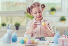 La jolie fille heureuse d'enfant ayant l'amusement pendant la peinture eggs pour l'est Photographie stock