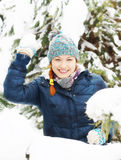 La jolie fille heureuse joyeuse joue des boules de neige dans la forêt d'hiver Image libre de droits