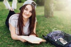 La jolie fille a lu le livre et écoute musique au parc Photographie stock