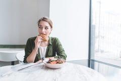 La jolie fille mange un sandwich dans un restaurant près de la fenêtre Pause de midi dans un restaurant avec un intérieur léger images stock