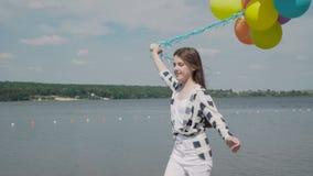La jolie fille marche sur la baie de rivière avec les ballons colorés et regarde sur l'eau clips vidéos