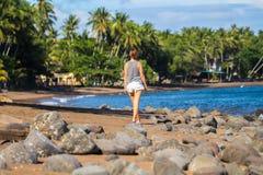 La jolie fille marche sur la plage Palmiers bleus de mer et de Cocos de bord de la mer romantique Images libres de droits