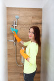 La jolie fille nettoie des salles de bains Photos stock