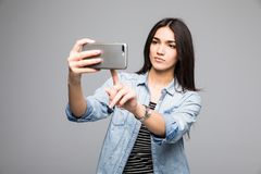 La jolie fille presse un doigt à un téléphone d'écran tactile sur le fond gris photos libres de droits