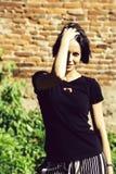 La jolie fille range des cheveux de brune image stock