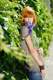 La jolie fille rousse avec le pourpre s'est levée Photographie stock