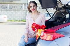 La jolie fille s'assied dans le tronc de voiture avec des tulipes Image stock
