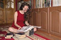 La jolie fille s'assied en position de lotus et l'information de recherche dans le livre d'art Image stock