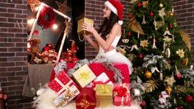 La jolie fille Santa Claus, portrait, beaucoup cadeau de Noël, boîtes de fête emballées, fille sexy choisit un cadeau pour vous banque de vidéos