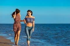 La jolie fille a un amusement avec son amie sur la plage Images libres de droits