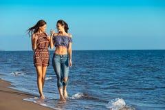 La jolie fille a un amusement avec son amie sur la plage Image libre de droits