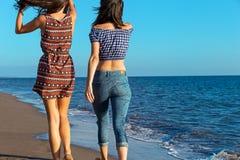 La jolie fille a un amusement avec son amie sur la plage Photo libre de droits