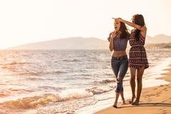 La jolie fille a un amusement avec son amie sur la plage Photographie stock