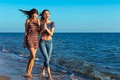La jolie fille a un amusement avec son amie sur la plage Photos libres de droits