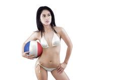 La jolie fille utilise le bikini et tient une boule Images stock