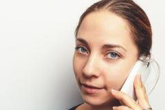 La jolie jeune femme à l'aide du téléphone portable et regardant l'appareil-photo, se ferment vers le haut du portrait avec l'esp Images stock