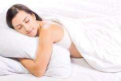 La jolie jeune femme dort dans le lit Photo stock