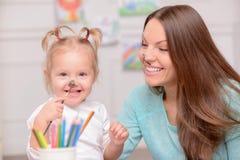 La jolie jeune femme enseigne son enfant à dessiner Image libre de droits