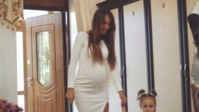 La jolie jeune femme et la petite fille marchent dans la chambre, souriant et allant lentement banque de vidéos