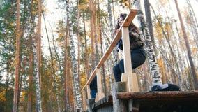 La jolie jeune femme marche à une barre transversale et s'assied sur un plancher sur une haute altitude banque de vidéos