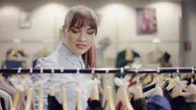 La jolie jeune femme marche par le support des vêtements dans un magasin d'habillement clips vidéos