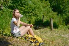 La jolie jeune femme se repose pendant une hausse dans les montagnes photo stock