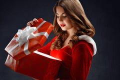La jolie jeune fille de neige ouvre le cadeau rouge d'abig pendant la nouvelle année 2018,2019 Photographie stock
