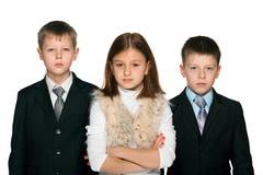 Jolie fille et deux garçons sérieux de Yong Photos libres de droits