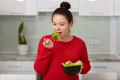 La jolie jeune future mère avec les cheveux foncés peignés dans le noeud, mange de la salade végétale savoureuse, utilise le chan photo libre de droits