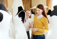 La jolie jeune mariée choisit l'équipement nuptiale au magasin de mariage Images stock
