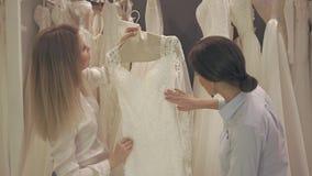 La jolie jeune mariée de sourire choisit la robe blanche à la boutique de la mode de mariage clips vidéos