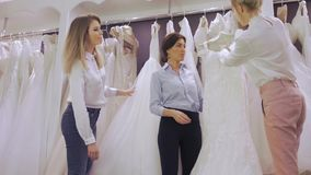 La jolie jeune mariée de sourire choisit la robe blanche à la boutique de la mode de mariage Heureux épousez le concept banque de vidéos