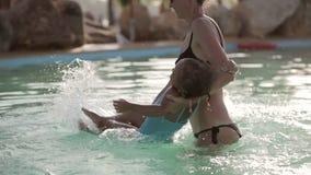 La jolie mère heureuse et sa fille ont un amusement dans la piscine banque de vidéos