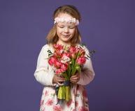 La jolie petite fille en guirlande des fleurs blanches regarde le bouquet des fleurs de tulipes de ressort pour la femme ou les m photos stock
