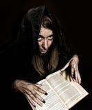 La jolie sorcière jette des sorts de livre antique épais par lueur d'une bougie sur un fond foncé Image libre de droits