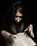 La jolie sorcière jette des sorts de livre antique épais par lueur d'une bougie sur un fond foncé Photos libres de droits