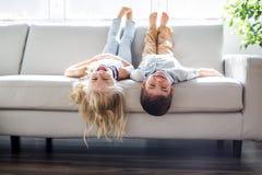 La jolis petite fille et garçon se trouvent sur leurs dos sur le sofa, l photographie stock