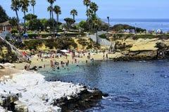 LA JOLLA, CA - 3 DE AGOSTO: Beachgoers que disfrutan de una tarde hermosa, soleada en la ensenada de La Jolla en San Diego, CA el Foto de archivo