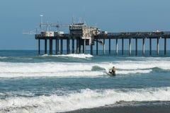 Female Surfer Heads Out to Sea Near Scripps Pier in La Jolla, California. LA JOLLA, CALIFORNIA/USA - APRIL 28, 2018:  A lone female surfer heads out to sea near Stock Images