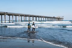Two Male Surfers Carrying Surfboards Near Scripps Pier in La Jolla. LA JOLLA, CALIFORNIA/USA - APRIL 28, 2018:  Two male surfers carrying surfboards enter the Royalty Free Stock Images